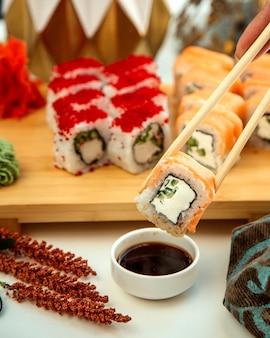 Sushi roll met rook zalm komkommer en room gedoopt in bijvoorbeeld saus