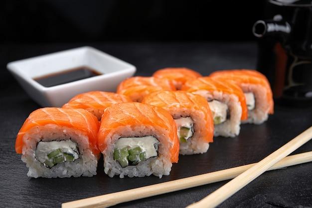 Sushi roll philadelphia, met roomkaas en zalm, op een zwarte achtergrond