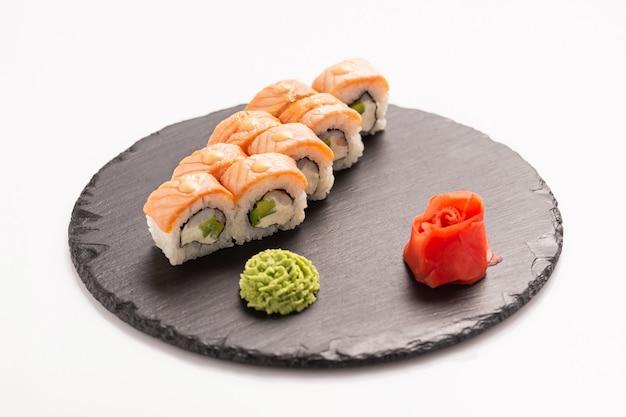 Sushi roll philadelphia met wasabi op de zwarte ronde steen