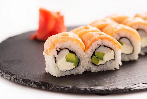 Sushi roll philadelphia op de zwarte ronde steen. detailopname.