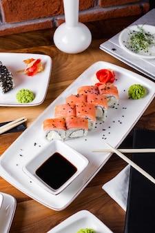 Sushi rolletjes met zalm geserveerd met sojasaus, gember en wasabi