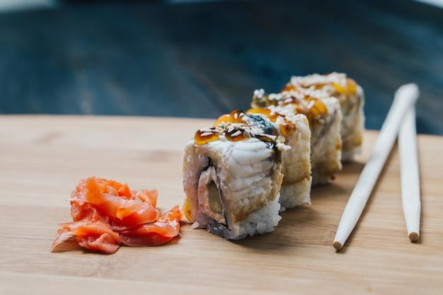 Sushi rolt eetstokjes gemberrood op een houten bord.