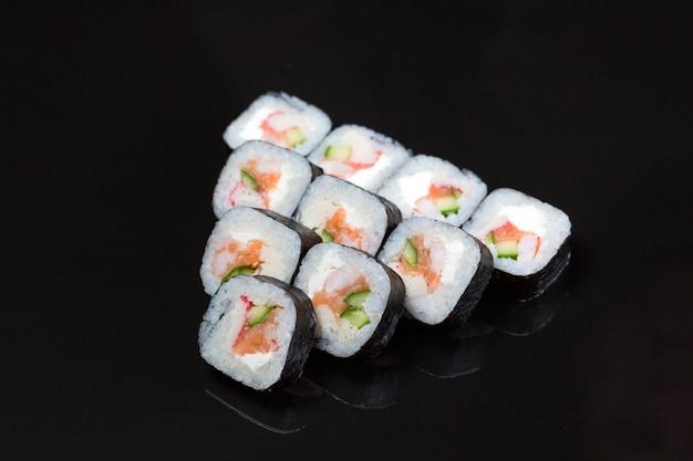 Sushi rolt futo maki op zwart.