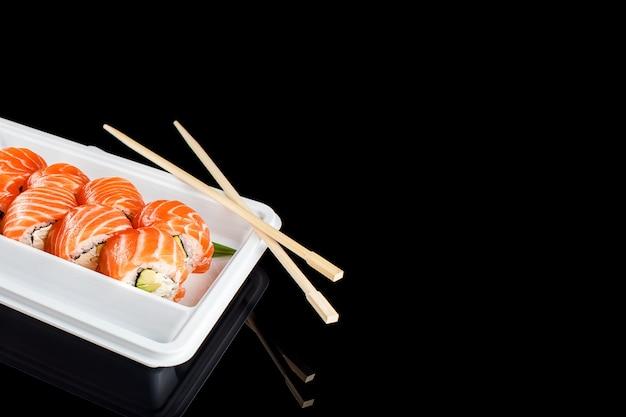 Sushi rolt gemaakt van verse rauwe zalm, roomkaas en avocado in witte plastic container klaar om te eten op zwarte achtergrond met reflecties