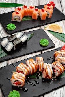 Sushi rolt geserveerd op planken op donkere houten achtergrond close-up