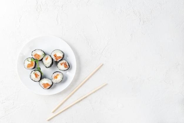 Sushi rolt in de vorm van een hart met stokjes op een witte plaat. valentijnsdag.