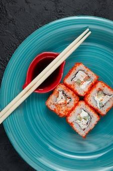 Sushi rolt in groene plaat op een donkere stenen achtergrond met bamboestokken en sojasaus