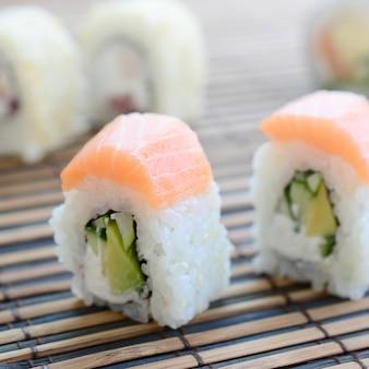 Sushi rolt leugens op een bamboe stro serwing mat. traditioneel aziatisch eten. ondiepe scherptediepte
