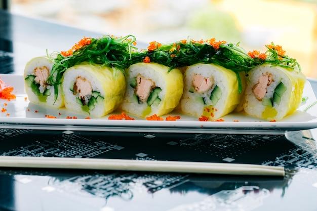 Sushi rolt met gebakken zalm en komkommer gegarneerd met zeewier