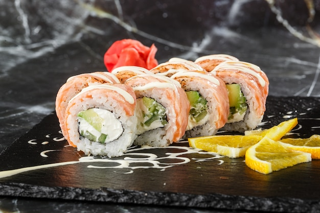 Sushi rolt met gevlamde zalm, komkommer en roomkaas binnen op zwarte leisteen geïsoleerd op zwart marmeren achtergrond. philadelphia roll sushi met komkommer. sushi menu. horizontale foto.
