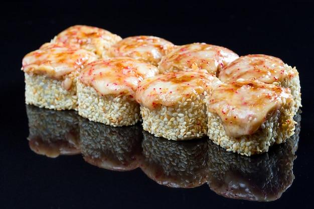Sushi rolt met inktvis, mossel en kaas op zwart.