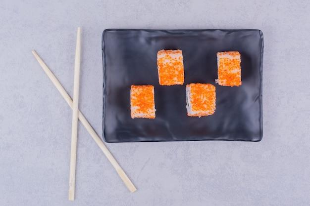 Sushi rolt met zalm in een zwarte keramische schotel.