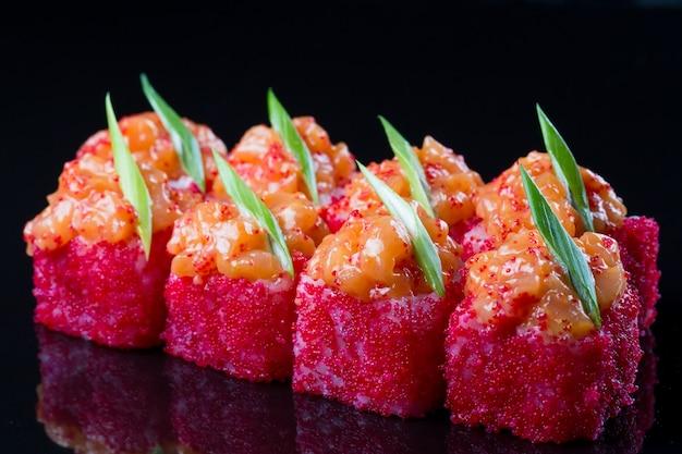 Sushi rolt met zalm, pikante saus op zwart.