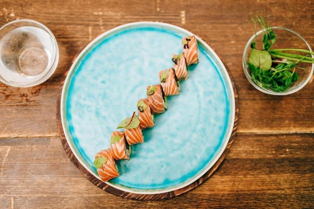 Sushi rolt met zalmvissen op plaat, bovenaanzicht, houten tafel