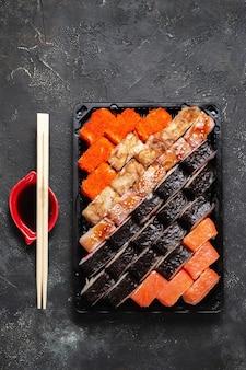 Sushi rolt op een donkere stenen achtergrond met bamboestokken en sojasaus