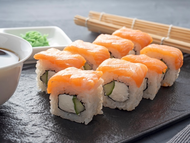 Sushi rolt philadelphia op een zwarte getextureerde plaat staan op een grijze achtergrond. wasabi gember en saus eetstokjes. broodjes met zalm, roomkaas, avocado.
