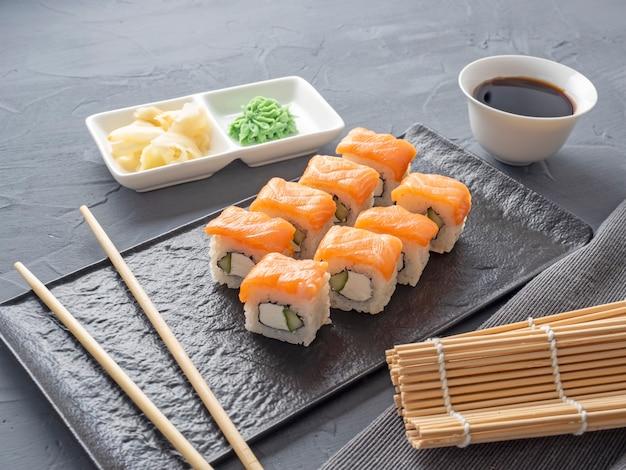 Sushi rolt philadelphia op een zwarte getextureerde plaatstandaard. wasabi-gember en sausstokjes. broodjes met zalm, roomkaas, avocado.