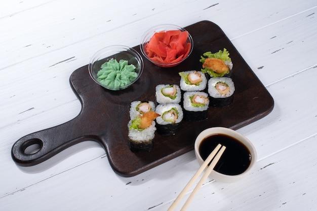 Sushi rolt set geserveerd op een donkere houten bord met wasabi, sojasaus en gember.