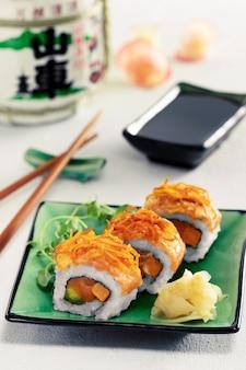 Sushi rolt set geserveerd op groene plaat op lichte achtergrond. menu concept.