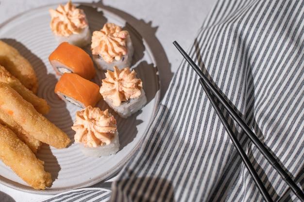 Sushi rolt set met zalm, kaasroom en gebakken garnalen op een grijze plaat