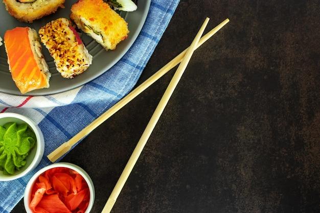 Sushi rolt van verschillende soorten op een donkere achtergrond bovenaanzicht met een plek voor een inscriptie