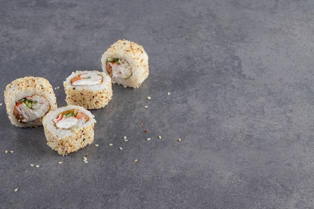 Sushi rolt versierde sesamzaadjes op stenen achtergrond.