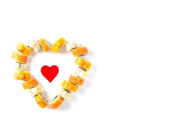 Sushi rolt voor valentijnsdag in de vorm van een hart op een witte achtergrond.