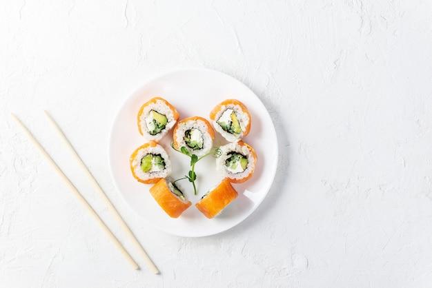 Sushi rolt voor valentijnsdag in de vorm van een hart op een witte plaat.