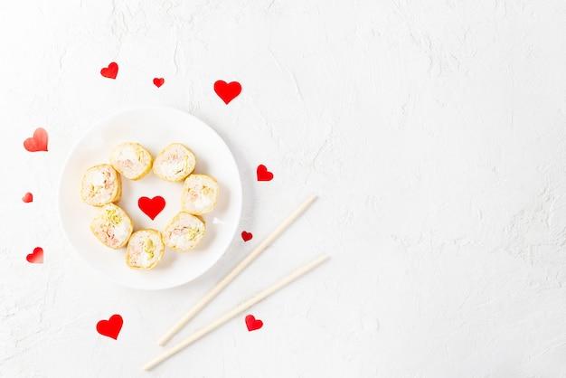 Sushi rolt voor valentijnsdag met rode harten op een witte plaat.