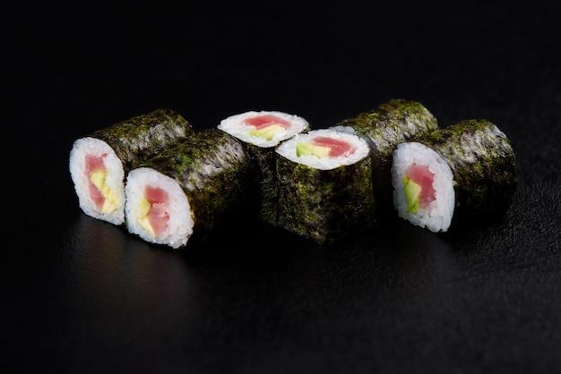 Sushi rolt zeevruchten. sushi bezorging vanuit het restaurant. verse heerlijke japanse sushi met avocado, komkommer, garnalen en kaviaar