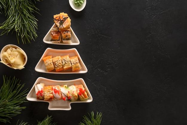 Sushi set geserveerd op plaat als kerstboom met decoratie van kerstmis op zwarte achtergrond.
