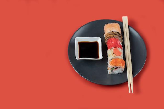 Sushi set met sauzen in een zwarte schotel op rode tafel.
