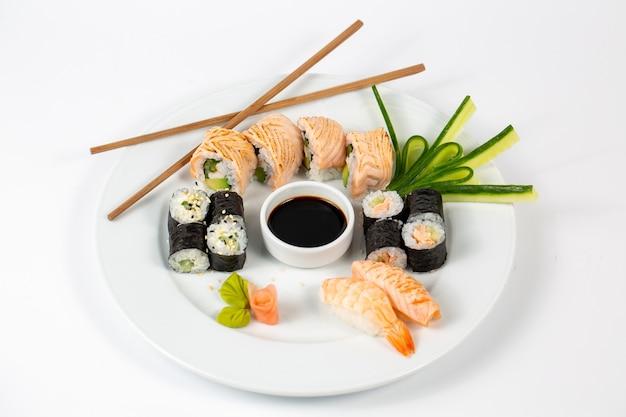 Sushi set met sojasaus in het midden van een bord en eetstokjes