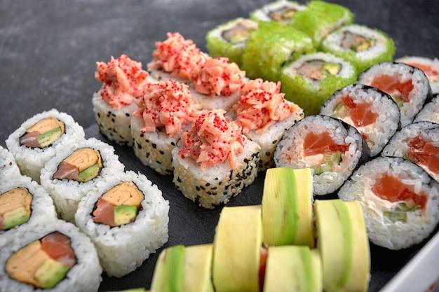 Sushi set van verschillende rollen, met kaviaar van vliegende vissen, tobiko, garnalen, paling, zalm, avocado, stokjes en sojasaus