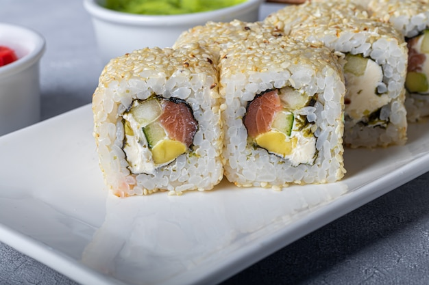Sushi sets nigiri, uramaki, californië, philadelphia, op een witte plaat. gember en wasabi in de buurt.