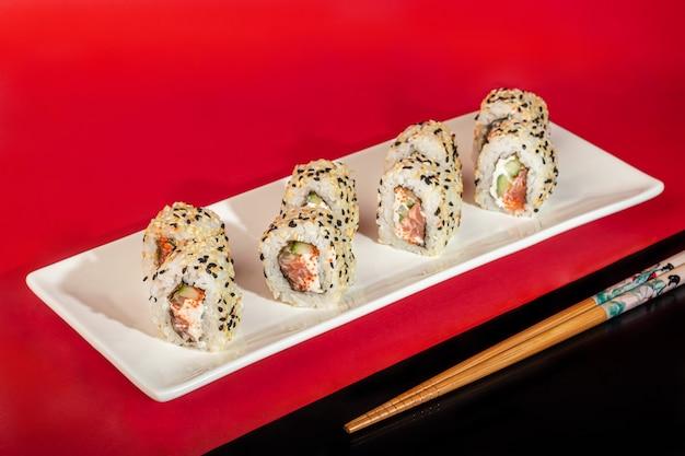 Sushi sets nigiri, uramaki, californië, philadelphia, op een witte plaat. op een rood gekleurde achtergrond. kopieer ruimte.