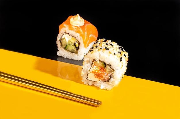 Sushi sets uramaki, californië, philadelphia, op een witte plaat. feestelijk, nieuwjaarsconcept. tegen een donkere reflecterende achtergrond. kopieer ruimte