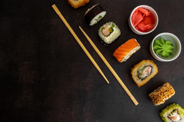 Sushi van verschillende soorten op een donkere achtergrond bovenaanzicht, met plaats voor tekst