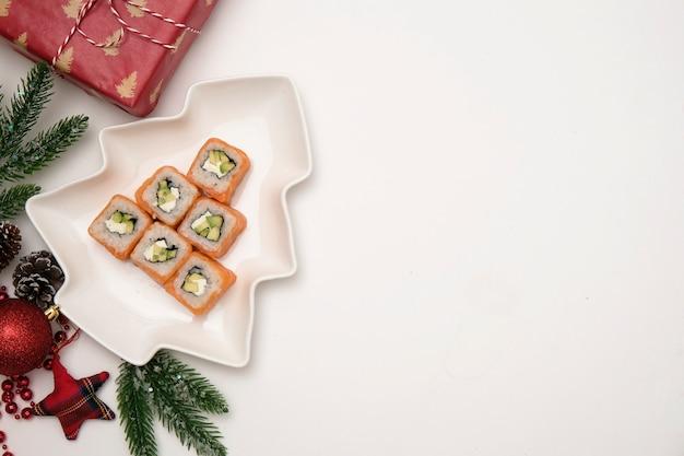 Sushi voor kerstmisconcept. eetbare kerstboom gemaakt van philadelphia roll op wit