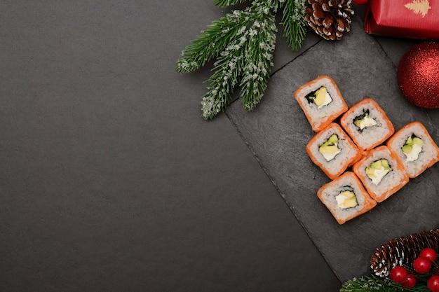 Sushi voor kerstmisconcept. eetbare kerstboom mde uit philadelphia roll op zwart