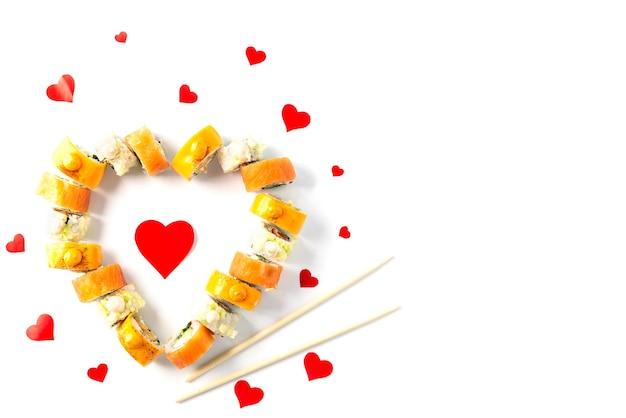 Sushi voor valentijnsdag in de vorm van een hart en eetstokjes.
