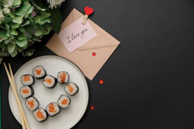 Sushi voor valentijnsdag - rol in hartvorm, op plaat op zwarte achtergrond. plat leggen. ruimte voor tekst.