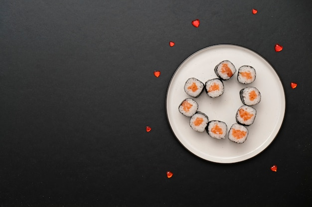 Sushi voor valentijnsdag - rol in hartvorm, op plaat op zwarte achtergrond. ruimte voor tekst.