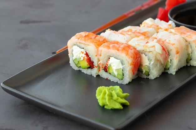 Sushibroodje bedekt met garnalenvlees op zwarte ceramische plaat dichte omhooggaand