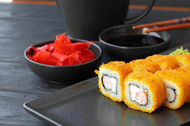 Sushibroodje dat in tempura op zwarte plaat wordt gebraden