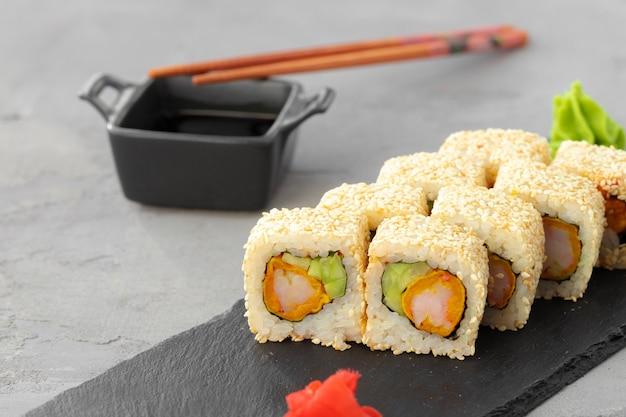 Sushibroodje met sesam op zwarte ceramische plaat dichte omhooggaand