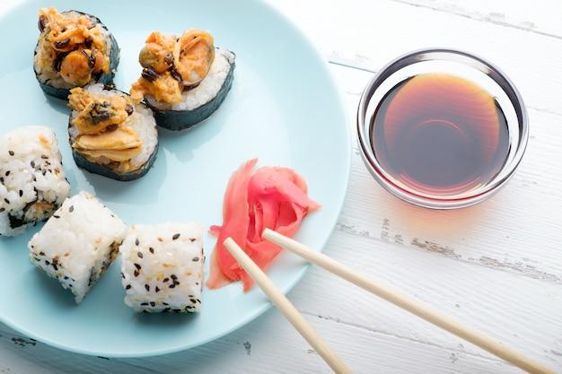 Sushibroodjes in blauw bord, eetstokjes en sojasaus