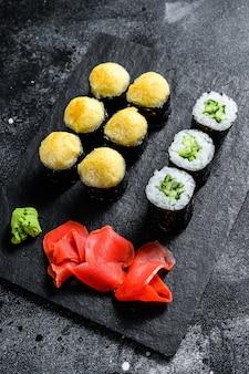 Sushibroodjes met komkommer, zalm en garnalen op een stenen dienblad. bovenaanzicht