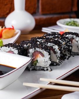 Sushibroodjes met sesamzaadjes geserveerd met sojasaus