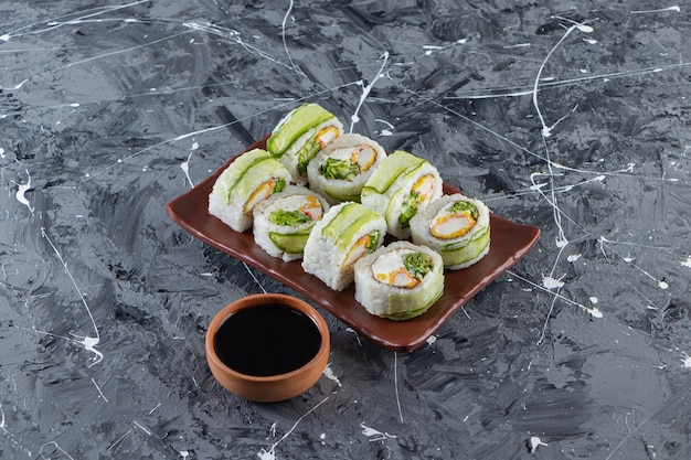 Sushibroodjes met sojasaus op een bruine plaat.